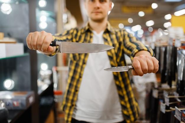 Młody człowiek trzyma noże kuchenne w sklepie agd. mężczyzna kupuje towary domowe na rynku, facet w sklepie z zaopatrzeniem w naczynia kuchenne