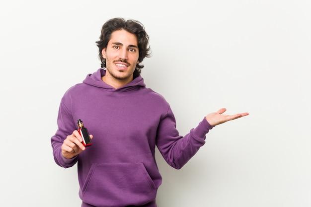 Młody człowiek trzyma odparowalnik pokazuje odbitkową przestrzeń na dłoni i trzyma inną rękę w talii.