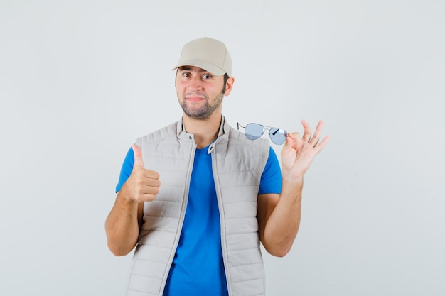 Młody człowiek trzyma okulary, pokazując kciuk w t-shirt, kurtkę, czapkę, widok z przodu.