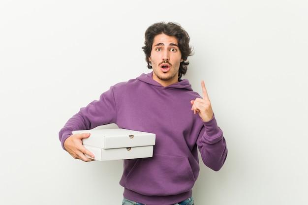 Młody człowiek trzyma pakiet pizzy mając jakiś świetny pomysł, pojęcie kreatywności.