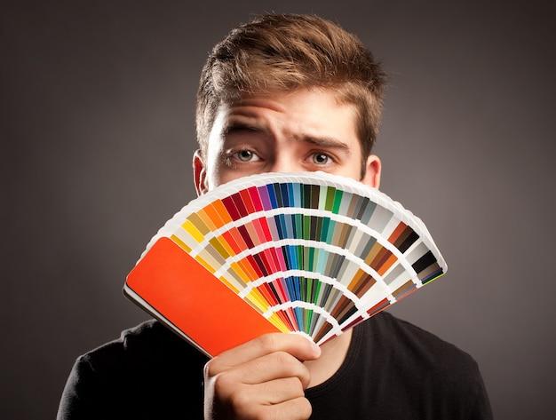 Młody człowiek trzyma paletę pantone