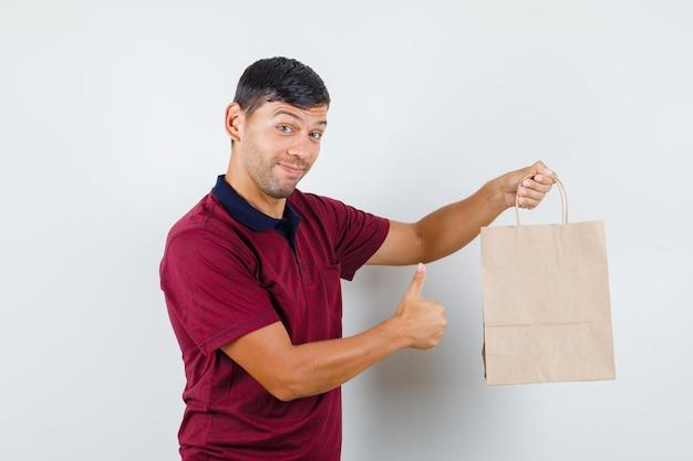 Młody człowiek trzyma papierową torbę z kciukiem w t-shirt i patrząc wesoły, widok z przodu.