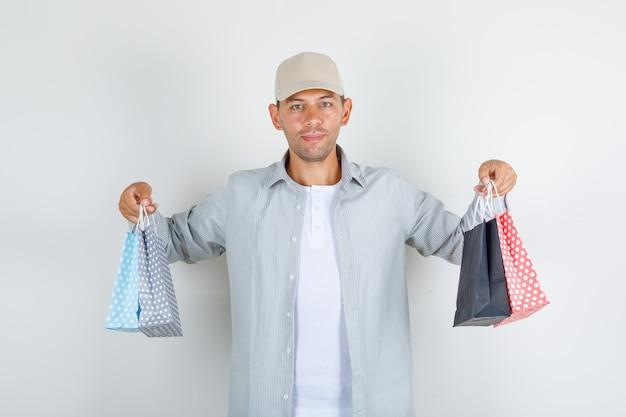 Młody człowiek trzyma papierowe torby w koszuli i czapce i wygląda wesoło