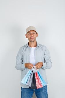 Młody człowiek trzyma papierowe torby w koszuli i czapce