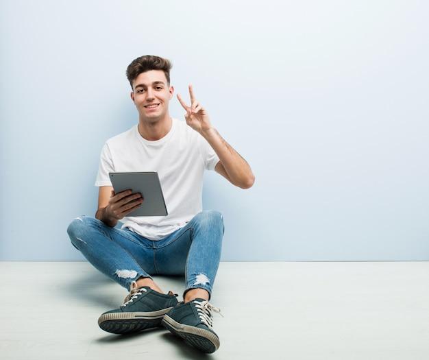 Młody człowiek trzyma pastylkę siedzi salowego pokazuje zwycięstwo znaka i ono uśmiecha się szeroko.
