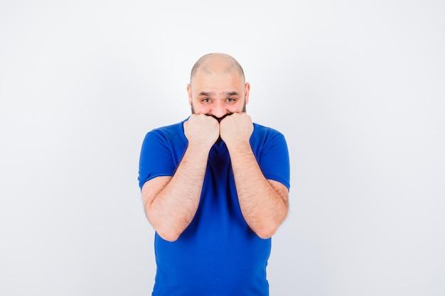 Młody człowiek trzyma pięści na ustach w niebieskiej koszuli i wygląda na przestraszony, widok z przodu.