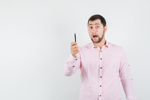 Młody człowiek trzyma pióro w różowej koszuli i wygląda zdziwiony