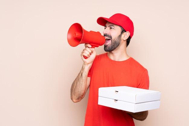 Młody człowiek trzyma pizzę krzyczy przez megafonu nad odosobnionym tłem
