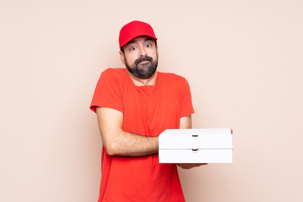 Młody człowiek trzyma pizzę robi wątpliwości gestowi podczas gdy podnoszący ramiona