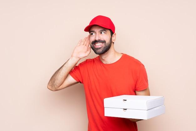 Młody człowiek trzyma pizzę słuchając czegoś, kładąc rękę na uchu