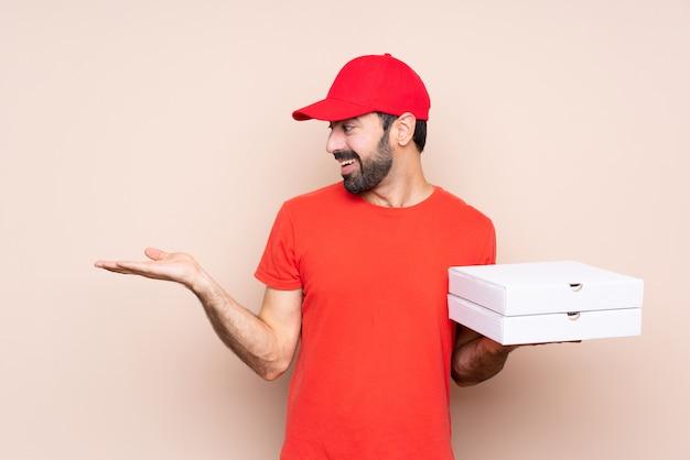 Młody człowiek trzyma pizzę z przedłużoną ręką