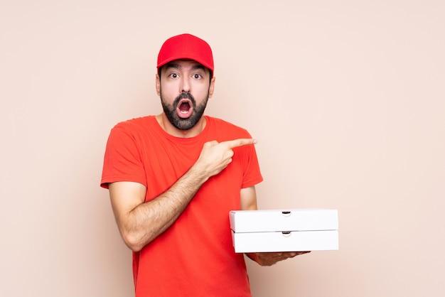 Młody człowiek trzyma pizzę zaskakującą i wskazuje stronę