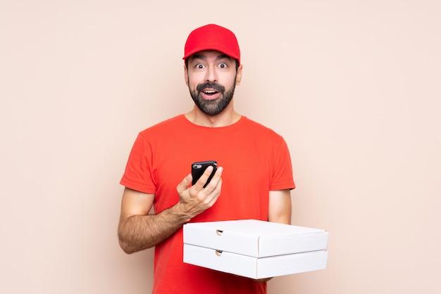 Młody człowiek trzyma pizzę zaskakującą i wysyła wiadomość