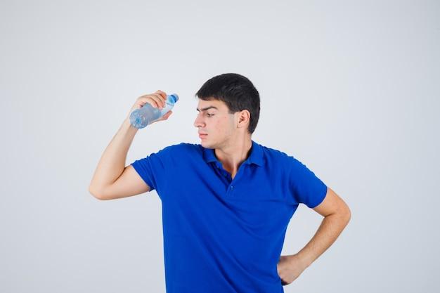 Młody człowiek trzyma plastikową butelkę podstępnie trzymając rękę w talii w t-shirt i patrząc pewnie. przedni widok.