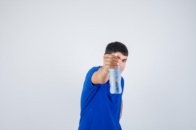 Młody człowiek trzyma plastikową butelkę w t-shirt i wygląda pewnie, widok z przodu.