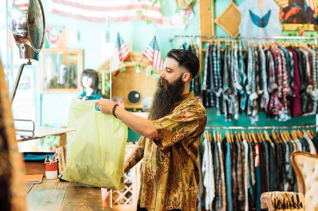 Młody człowiek trzyma plastikową torbę w butiku