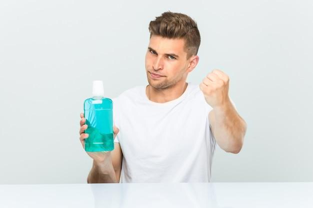 Młody człowiek trzyma płyn do płukania ust pokazując pięść z agresywnym wyrazem twarzy.