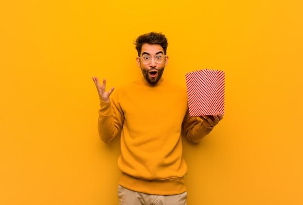 Młody człowiek trzyma popcorns świętuje zwycięstwo lub sukces