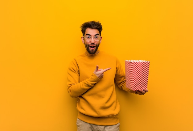 Młody człowiek trzyma popcorns trzyma coś ręką