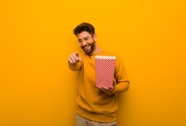 Młody człowiek trzyma popcorns wesoły i uśmiechnięty