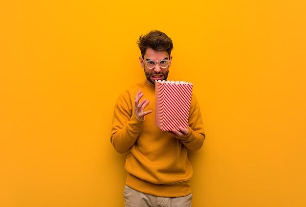 Młody człowiek trzyma popcorns zły i zdenerwowany