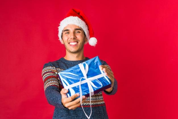 Młody człowiek trzyma prezent na święto bożęgo narodzenia