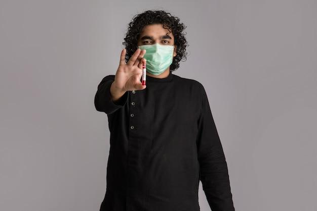 Młody człowiek trzyma probówkę z próbką krwi do koronawirusa lub analizy 2019-ncov.