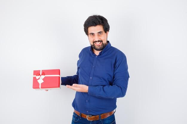 Młody człowiek trzyma pudełko i wskazując na to w niebieskiej koszuli i dżinsach i patrząc optymistycznie, widok z przodu.