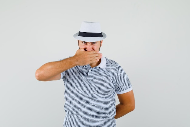 Młody człowiek trzyma rękę na ustach w t-shirt, kapelusz i patrząc uparty, widok z przodu.