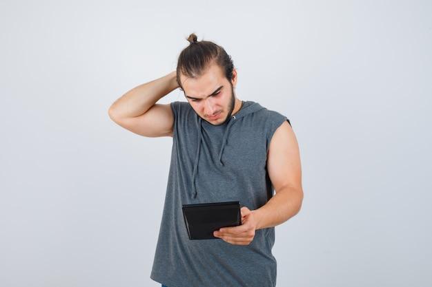 Młody człowiek trzyma rękę za głową, patrząc na kalkulator w bluzie z kapturem i patrząc zamyślony, widok z przodu.