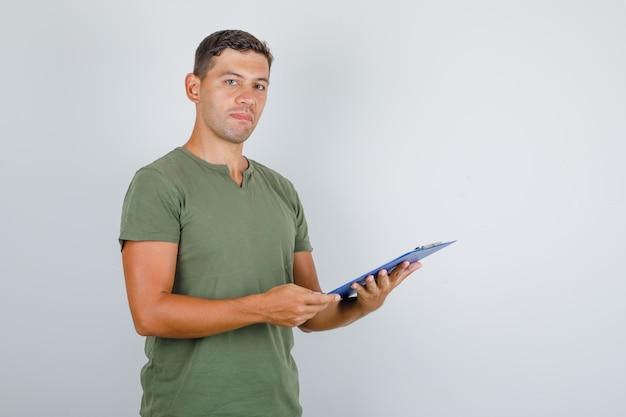 Młody człowiek trzyma schowek w wojskowej zielonej koszulce, widok z przodu.
