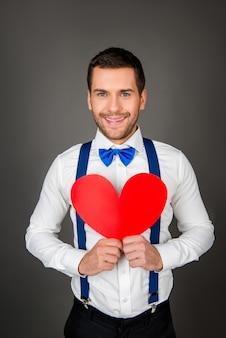 Młody człowiek trzyma serce czerwony papier