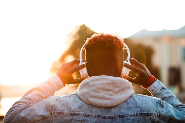 Młody człowiek trzyma słuchawki na głowie