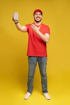 Młody człowiek trzyma smartfon na białym tle na żółtej ścianie