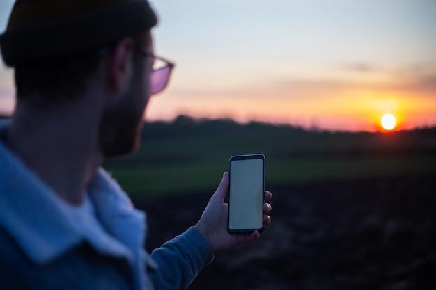 Młody człowiek trzyma smartfon z pustą białą makietą na tle zachodu słońca