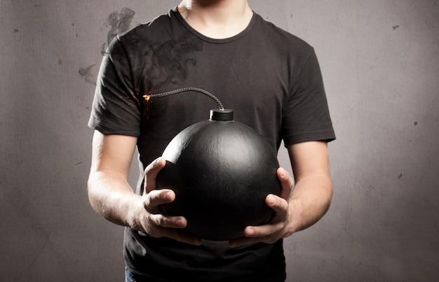 Młody człowiek trzyma staromodną bombę