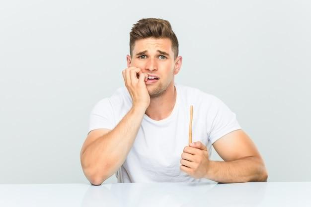 Młody człowiek trzyma szczoteczkę do zębów obgryzający paznokcie, nerwowy i bardzo niespokojny.