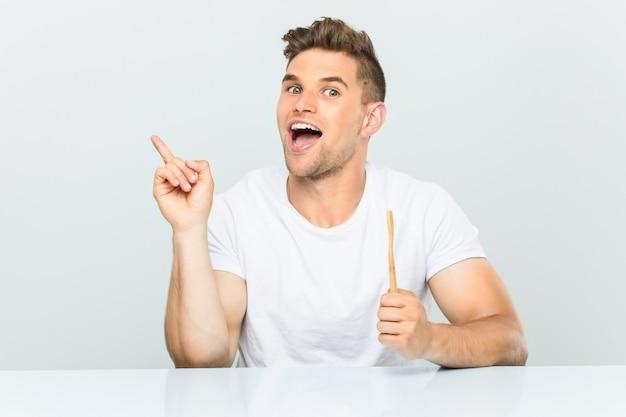 Młody człowiek trzyma szczoteczkę do zębów uśmiecha się wesoło wskazując palcem wskazującym daleko.