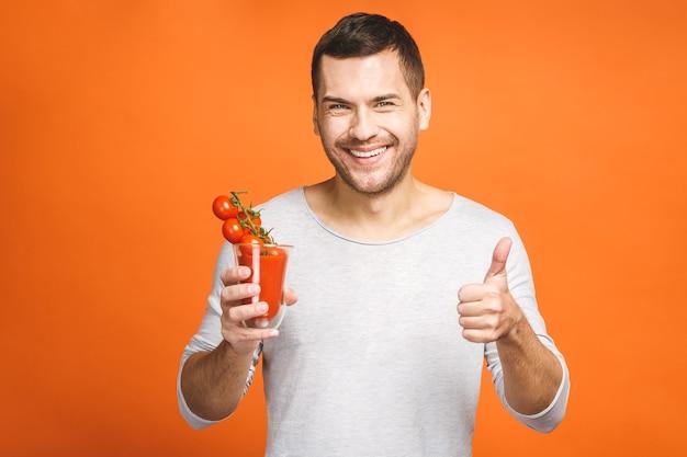 Młody człowiek trzyma szklankę soku i zjada warzywa na białym tle na pomarańczowym tle