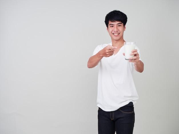 Młody człowiek trzyma szklankę świeżego mleka.