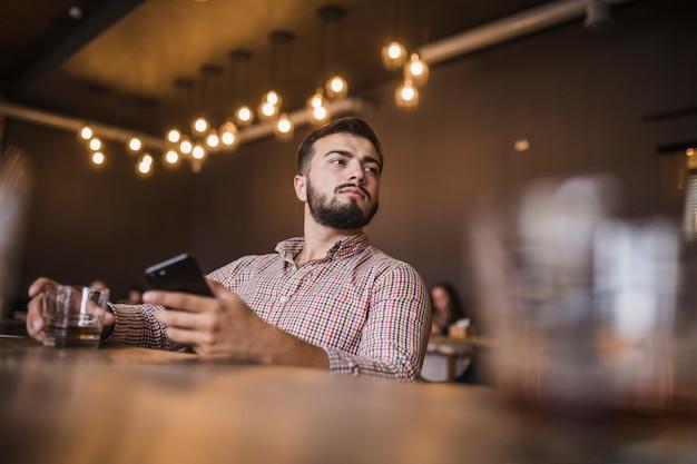 Młody człowiek trzyma szkło napój i telefon komórkowy patrzeje daleko od