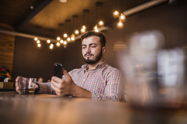 Młody człowiek trzyma szkło napój używać telefon komórkowego