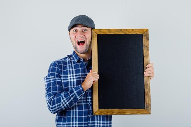 Młody człowiek trzyma tablicę w koszuli, czapkę i patrząc wesoło, widok z przodu.