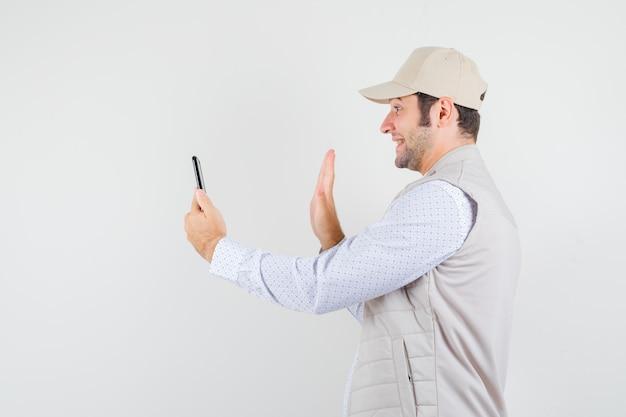 Młody człowiek trzyma telefon komórkowy i rozmawia z kimś za pośrednictwem połączenia wideo w beżowej kurtce i czapce i szuka szczęśliwy, widok z przodu.