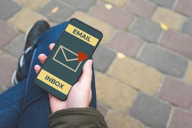 Młody człowiek trzyma telefon komórkowy z miłością e-mail