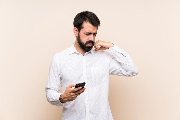 Młody człowiek trzyma telefon komórkowy z zmęczonym i chorym wyrażeniem z brodą