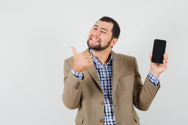 Młody człowiek trzyma telefon komórkowy