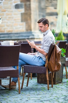 Młody człowiek trzyma telefon na zewnątrz na ulicy. facet za pomocą smartfona.