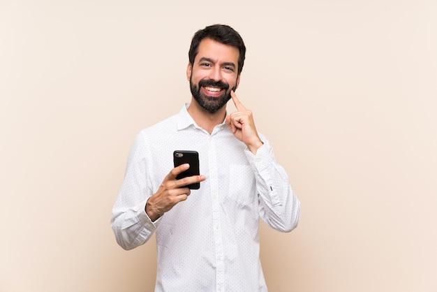 Młody człowiek trzyma telefon z brodą ono uśmiecha się z szczęśliwym i przyjemnym wyrażeniem