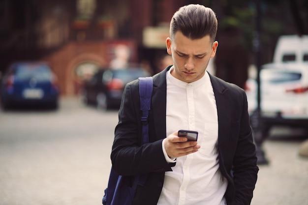 Młody człowiek trzyma telefon z plecakiem